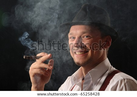Portrait of the young man against a dark background in the black hat, smoking the big cigar.