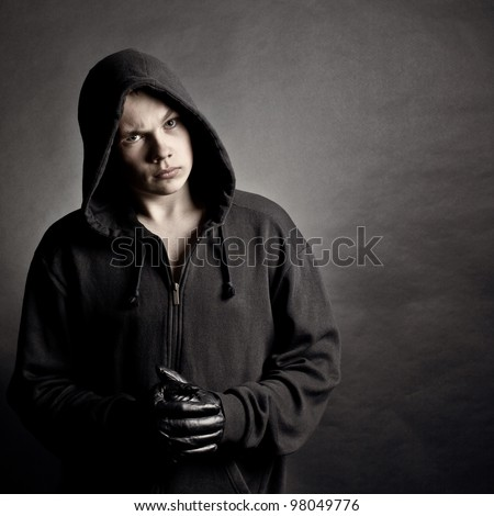 Portrait of the young man in a hood against a dark background - stock photo
