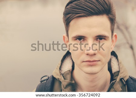 Portrait of the young man on the river in vintage style - stock photo