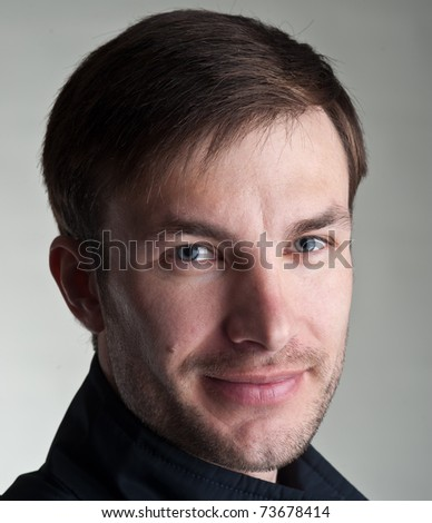 Portrait of the young nice man on a light background, a close up
