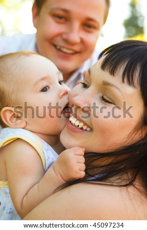 Portrait of the young parents  playing with their baby son - stock photo