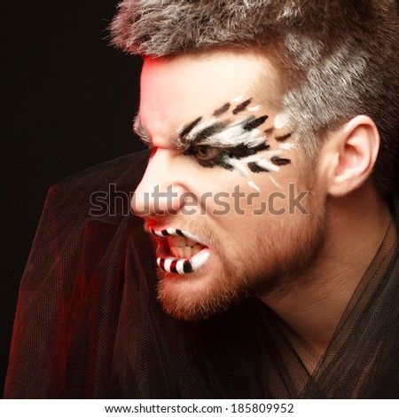 portrait of the young shouting man. body art - stock photo