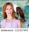 Portrait of the young woman with a prey bird on a shoulder. - stock photo