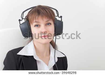 Portrait of the young woman with the big ear-phones on a head
