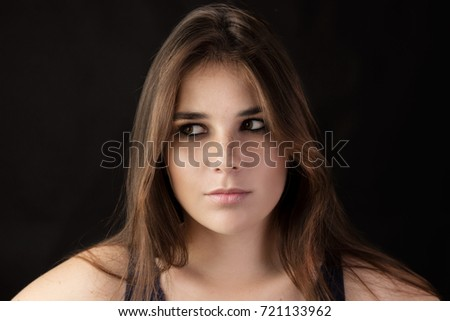 Portrait of thinking black haired and green eyed woman with black background