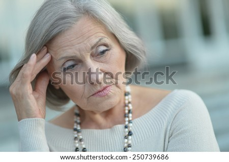 Portrait of thinking elderly woman - stock photo