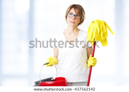 Portrait of thinking middle age woman holding in her hand mop and mopping bucket. - stock photo