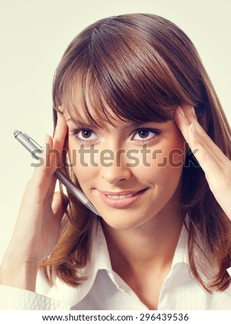 Portrait of thinking or planning young businesswoman in white business style clothing or student with pen - stock photo