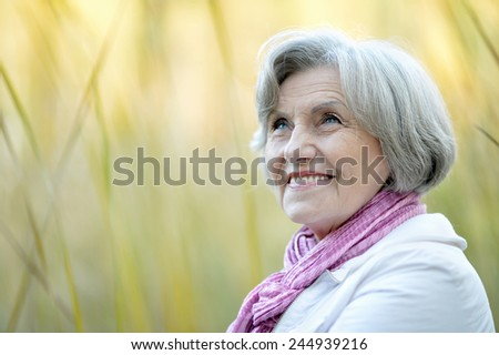 Portrait of thinking senior woman in autumn park - stock photo