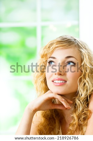 Portrait of thinking young beautiful blond woman, at home, with copyspace - stock photo
