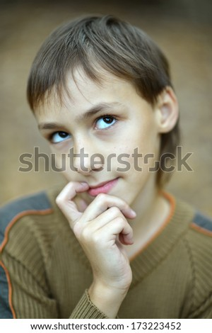 Portrait of thinking young boy in autumn park - stock photo