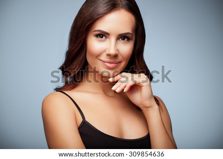 portrait of thinking young woman in black tank top clothing, on grey background - stock photo