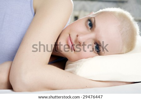 portrait of thoughtful blond bald woman lying on the bed