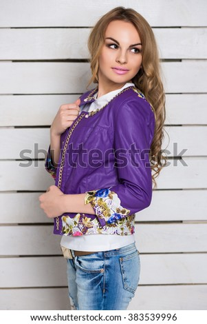 Portrait of thoughtful blond woman in purple jacket posing near the white wooden wall - stock photo