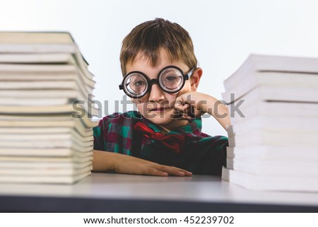 Portrait of thoughtful boy amidst books on table in classroom - stock photo