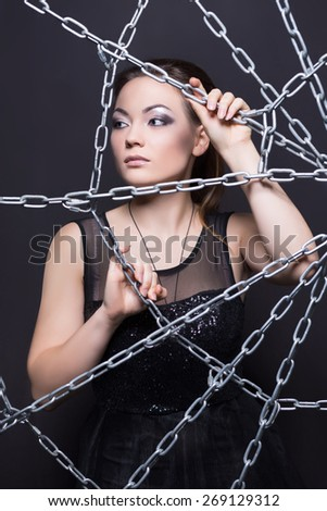 Portrait of thoughtful brunette in black dress posing behind the web of chains - stock photo