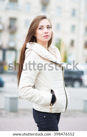 Portrait of thoughtful brunette in white jacket posing outdoors - stock photo