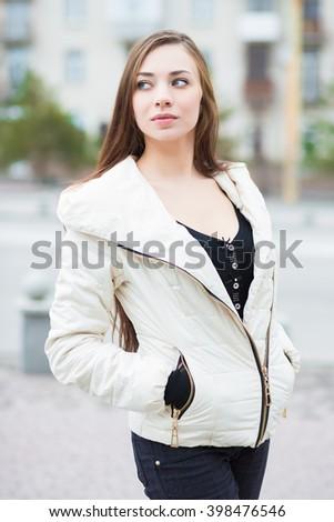 Portrait of thoughtful brunette wearing white jacket posing outdoors - stock photo
