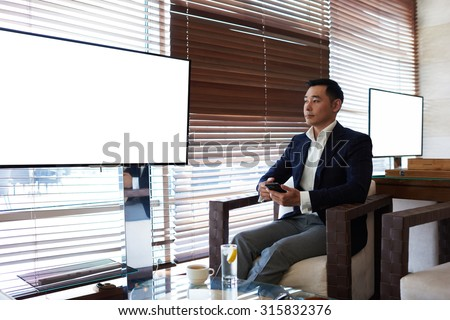 Portrait of thoughtful businessman holding cell telephone while sitting in modern cafe near empty screen with copy space area, intelligent man in luxury suit using smart phone while sitting in office - stock photo