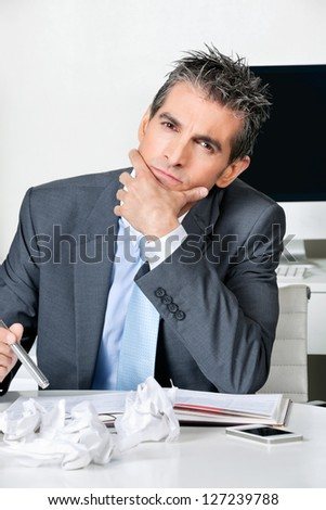 Portrait of thoughtful businessman sitting at desk in office