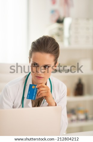Portrait of thoughtful doctor woman with credit card