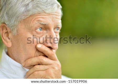 Portrait of thoughtful elderly man on autumn background