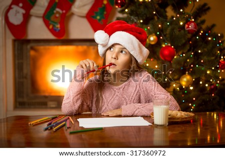 Portrait of thoughtful girl in Santa cap thinking of letter with gift wishes - stock photo
