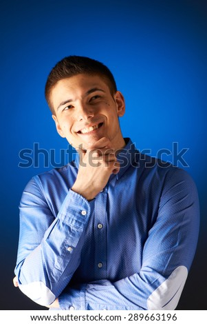 Portrait of thoughtful man against blue background - stock photo