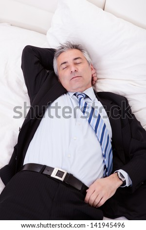 Portrait Of Thoughtful Mature Businessman Relaxing On Bed - stock photo