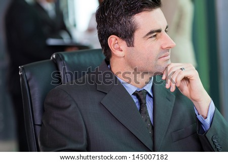 portrait of thoughtful middle aged businessman in office - stock photo