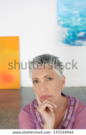Portrait of thoughtful senior woman with hand on chin in art gallery - stock photo