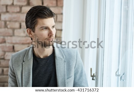 Portrait of thoughtful young man standing front of window, looking away. - stock photo