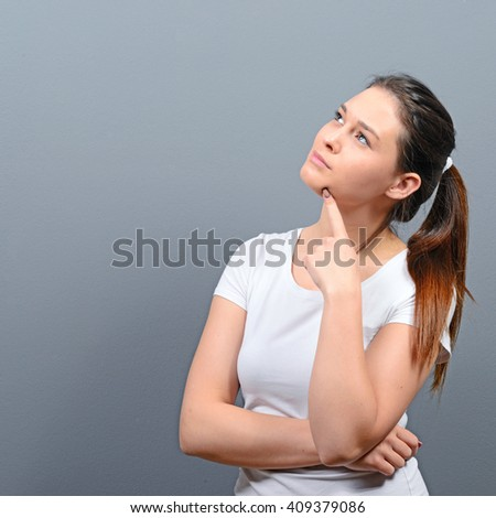 Portrait of thoughtful young woman looking above against gray background - stock photo