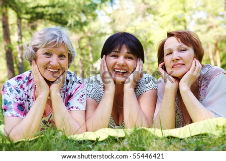 Portrait of three aged women resting on grass and looking at camera with smiles - stock photo