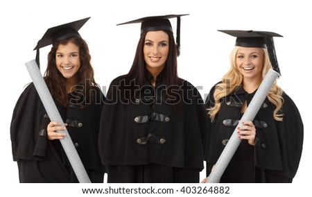 Portrait of three attractive female graduates smiling happy in academic dress, holding diploma. - stock photo