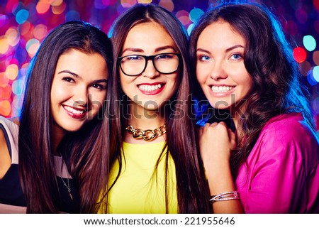 Portrait of three attractive girls in nightclub - stock photo