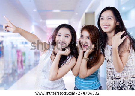Portrait of three beautiful teenage girls in the shopping center and looks happy when looking at a shop - stock photo