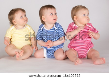 Portrait of three beautiful toddlers sitting in line looking to the right - stock photo