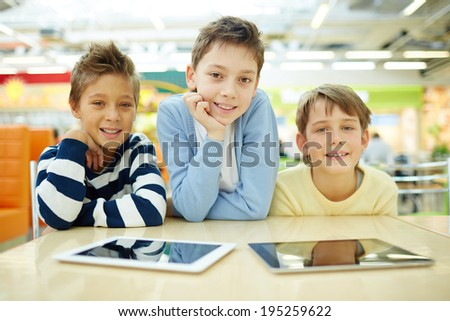 Portrait of three boys with touchpads sitting in cafe and looking at camera - stock photo