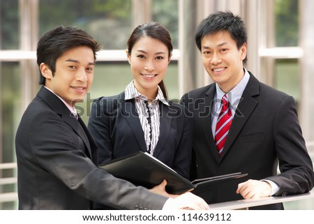 Portrait Of Three Business Colleagues Discussing Document Outside Office - stock photo