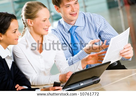 Portrait of three business partners sitting at the table with a laptop on it and looking at the document in the businessman's hands