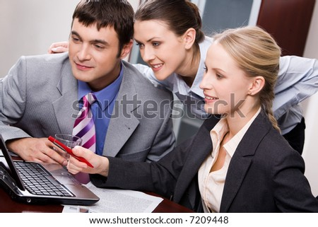 Portrait of three business people looking at a monitor of laptop
