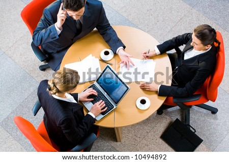 Portrait of three business person sitting at the round table - stock photo