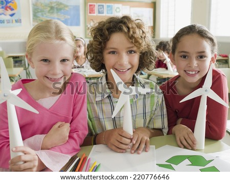 Portrait of three children looking to camera with paper windmills illustrating alternative energy in a school classroom - stock photo