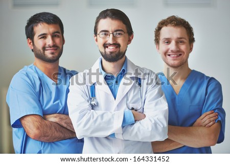 Portrait of three clinicians in uniform looking at camera with smiles - stock photo