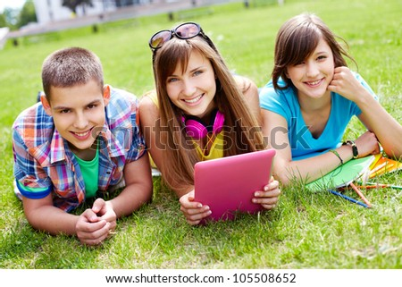 Portrait of three college students enjoying their free time outdoors - stock photo