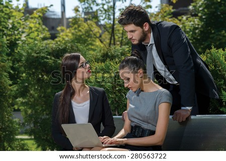 Portrait of three  confident and motivated business partners. Businessman is standing while his colleagues are sitting and discussing business details of current projects.  Outdoor business concept - stock photo