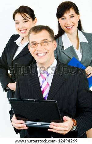 Portrait of three confident business partners looking at camera with smiles with leader holding laptop in front - stock photo