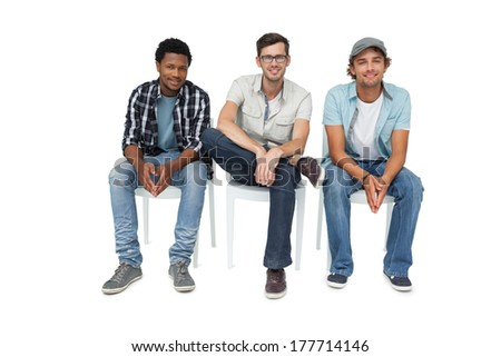 Portrait of three cool young men sitting on chairs over white background - stock photo