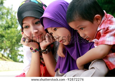 Portrait of three cute sibling outdoor together - stock photo